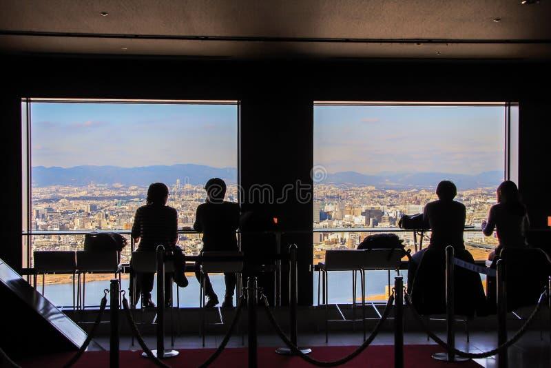Siluetas de los hombres que se sientan por la ventana grande en fondo de la vista panorámica de Osaka fotos de archivo