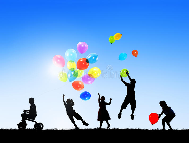 Siluetas de los niños que juegan los globos al aire libre fotografía de archivo libre de regalías
