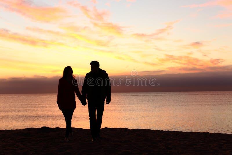 Siluetas de los pares que caminan junto en la puesta del sol imagenes de archivo