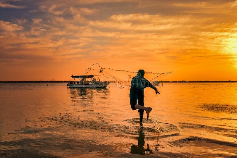 Siluetas de los pescadores que lanzan la red de pesca durante puesta del sol en la playa la Arabia Saudita de Dammam fotos de archivo