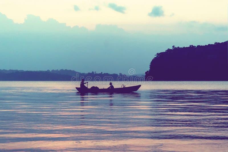 siluetas de los pescadores de sexo masculino en la puesta del sol imágenes de archivo libres de regalías