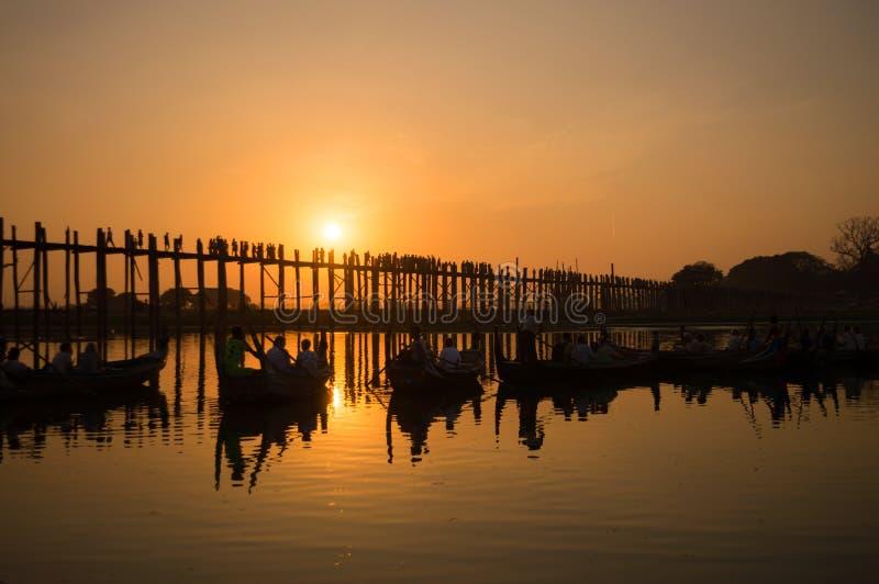Siluetas de los turistas en barcos que admiran el puente de U Bein sobre el lago Taungthaman en la puesta del sol, en Amarapura,  imágenes de archivo libres de regalías