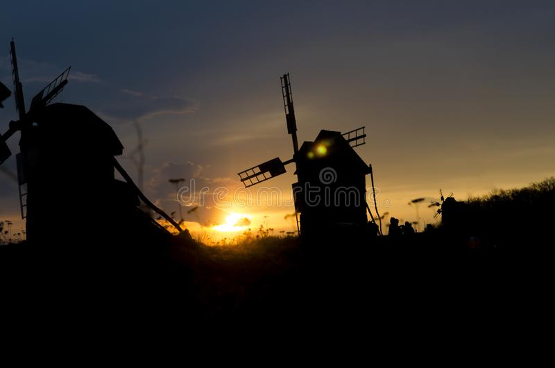 Siluetas de molinoes de viento viejos en el fondo de la puesta del sol brillante del cielo azul imágenes de archivo libres de regalías