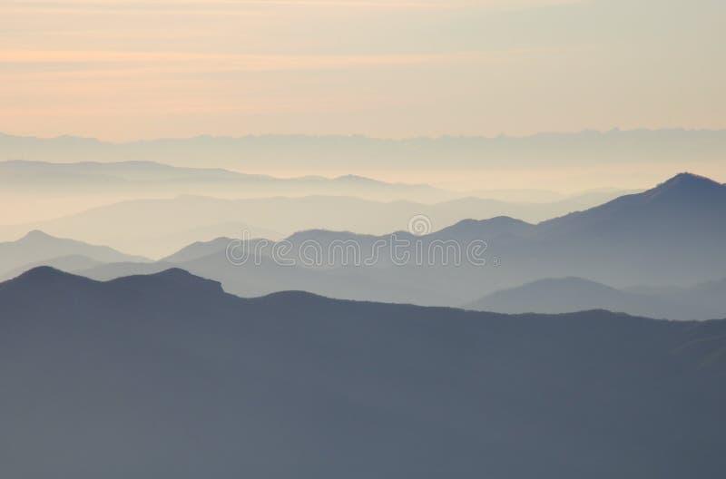 Siluetas de montañas en la niebla en la puesta del sol imagen de archivo