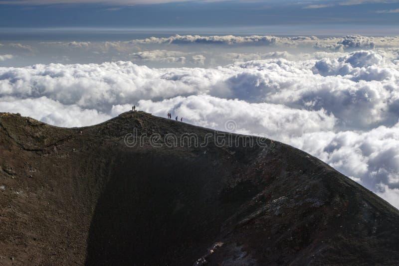 Siluetas de montañeses sobre las nubes en el borde de un cráter extinto en el volcán el Etna fotografía de archivo