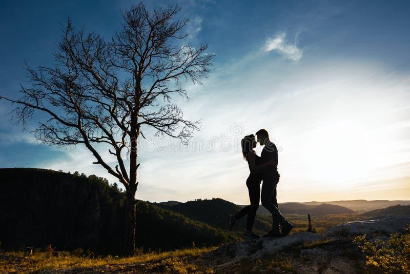Siluetas de pares cariñosos en la puesta del sol fotografía de archivo libre de regalías