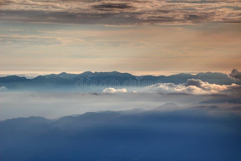 Siluetas de Ridge en la niebla Bohinj Julian Alps del otoño que brilla intensamente imagenes de archivo