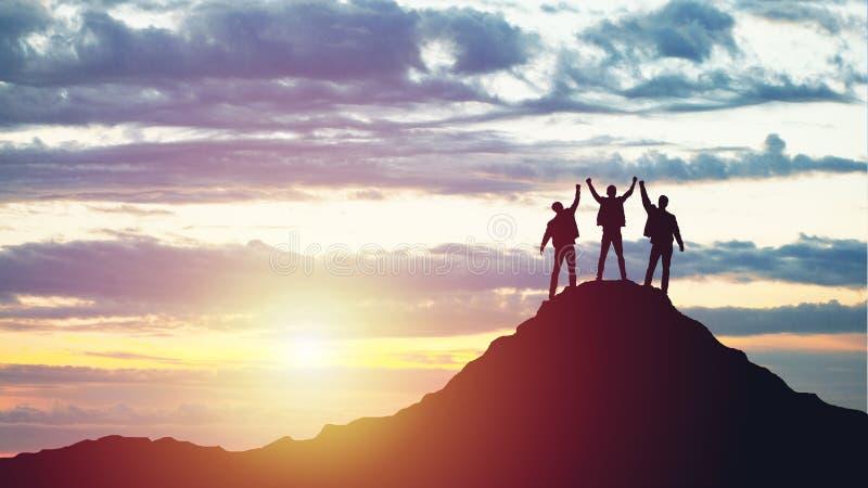 Siluetas de tres personas felices encima de una montaña imagen de archivo