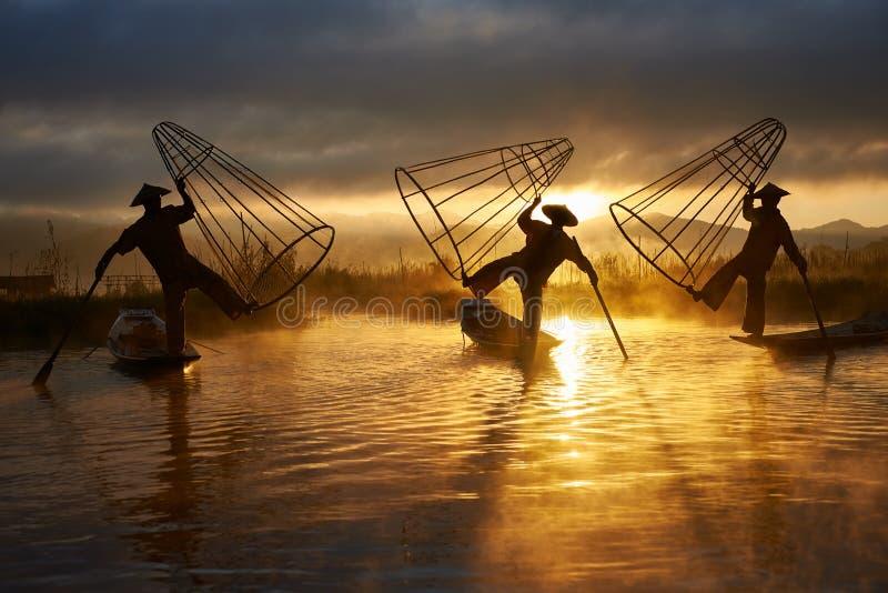 Siluetas de tres pescadores en el lago Myanmar Inle fotografía de archivo