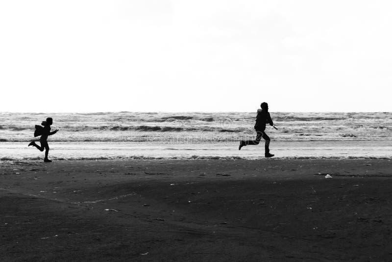 Siluetas de un hermano y de un funcionamiento de la hermana salvajes y libres en la playa imagen de archivo