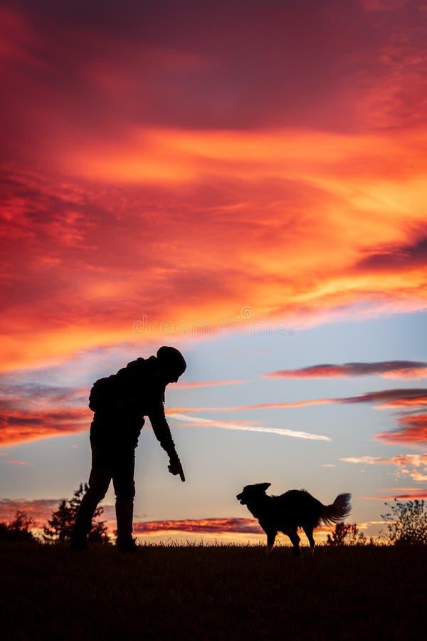 Siluetas de un hombre y de su perro delante de un fondo de la puesta del sol o de la salida del sol fotografía de archivo