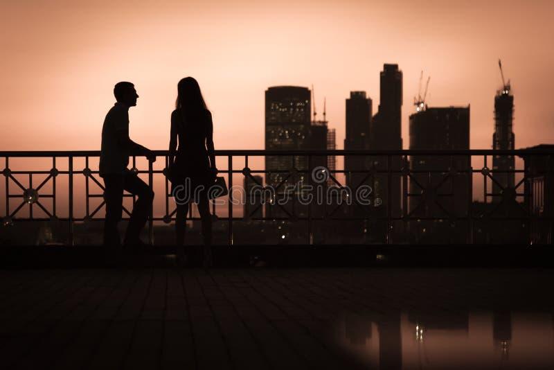Siluetas de un par de gente joven en amor en la puesta del sol en evenning en ciudad grande foto de archivo