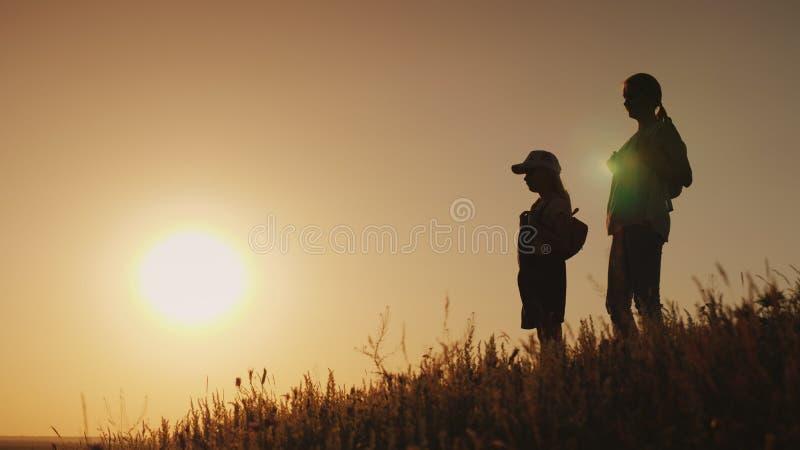 Siluetas de una mujer con un niño Se colocan con las mochilas detrás de su parte posterior, ellos admiran la puesta del sol trave fotografía de archivo libre de regalías