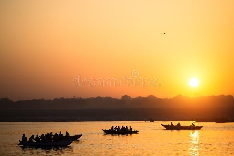 Siluetas del barco con los peregrinos durante puesta del sol asombrosa en el río Ganges santo, Varanasi imagen de archivo libre de regalías