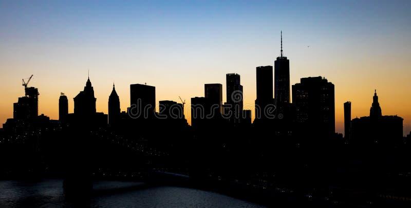 Siluetas del edificio del horizonte de New York City en la oscuridad con el cielo crepuscular del color sobre Manhattan foto de archivo libre de regalías