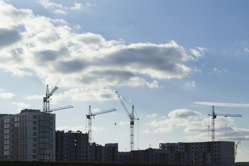 Siluetas del emplazamiento de la obra con los edificios y las gr?as inacabados contra el cielo con las nubes fotografía de archivo libre de regalías