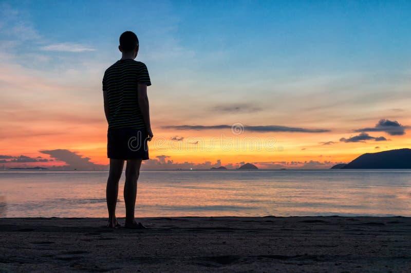 Siluetas del hombre en la playa en una salida del sol colorida con el cielo que sorprende sobre el oc?ano fotografía de archivo libre de regalías