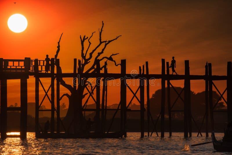 Siluetas en el puente de la teca de U Bein en la puesta del sol Myanmar (Birmania) foto de archivo