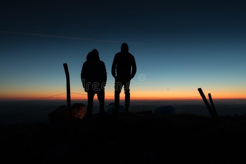 Siluetas en una puesta del sol colorida foto de archivo