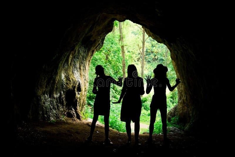Siluetas femeninas en la entrada a la cueva natural en el m?s forrest fotografía de archivo libre de regalías