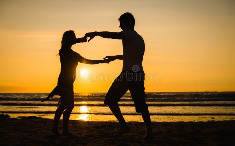 Siluetas hermosas de bailarines en la puesta del sol foto de archivo libre de regalías