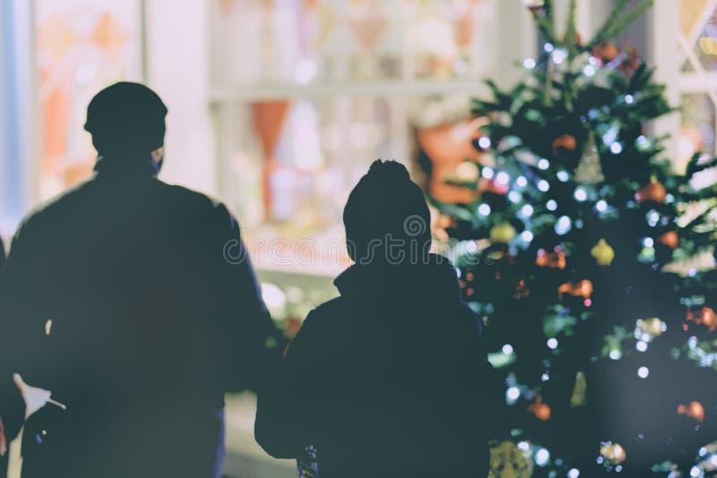 Siluetas irreconocibles de la ventana cercana de la tienda de la gente, árbol de navidad con las decoraciones La Navidad shoping imagen de archivo libre de regalías