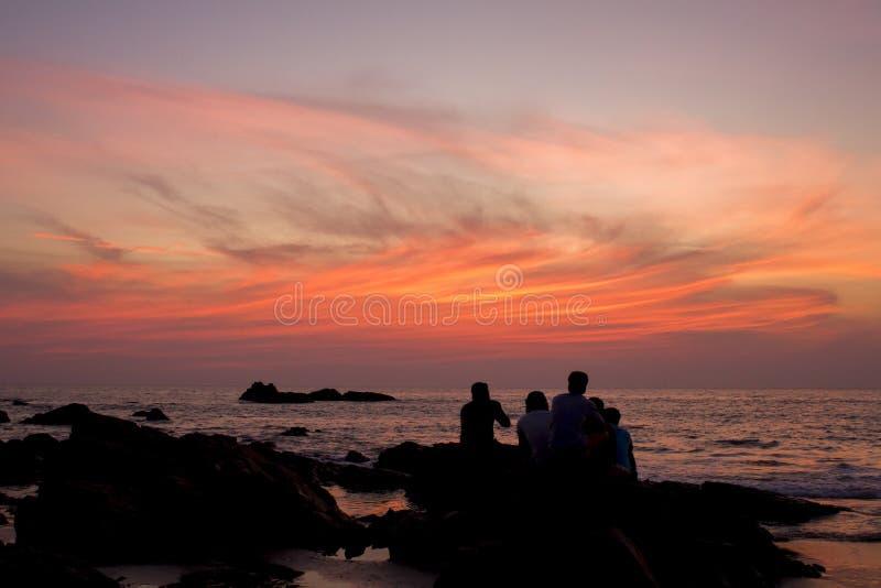 Siluetas negras de los amigos que se sientan en piedras contra el océano y el cielo azul rosado púrpura de la puesta del sol foto de archivo libre de regalías