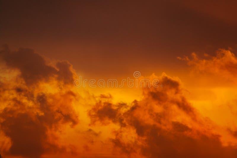 Siluetas oscuras de nubes en el cielo anaranjado imagenes de archivo