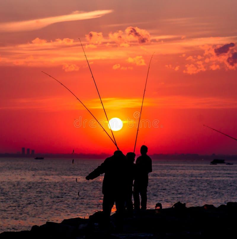 Siluetas rojas intensas de la puesta del sol y de los pescadores fotografía de archivo