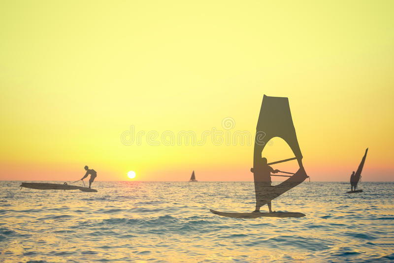 Siluetas transparentes de las personas que practica surf del viento en la puesta del sol imagen de archivo