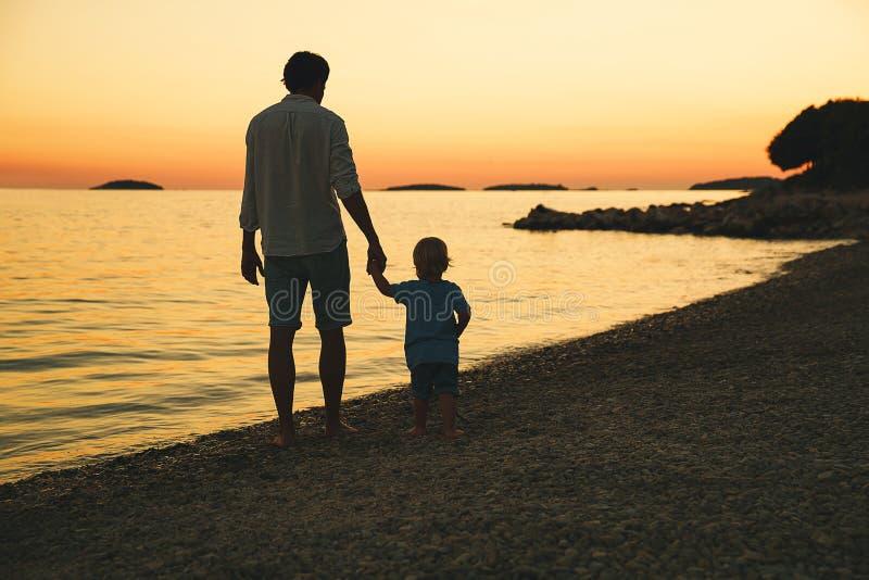 Siluetas traseras del padre y del hijo que caminan por el mar foto de archivo libre de regalías