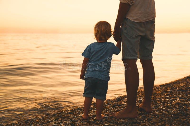 Siluetas traseras del padre y del hijo que caminan por el mar imagen de archivo libre de regalías