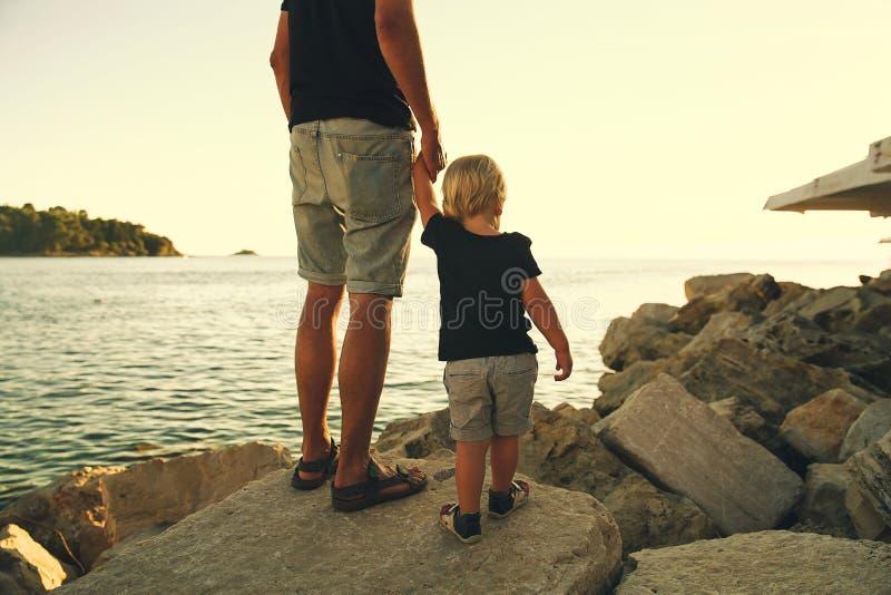 Siluetas traseras del padre y del hijo que caminan por el mar imágenes de archivo libres de regalías