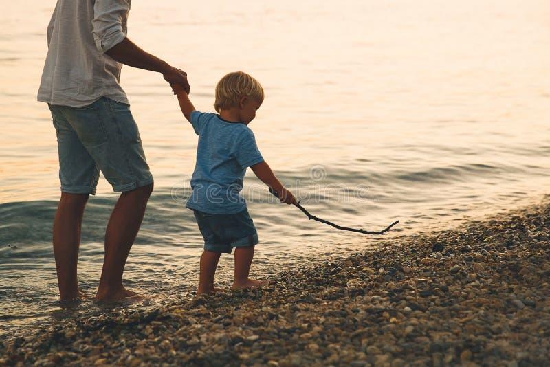 Siluetas traseras del padre y del hijo que caminan por el mar foto de archivo