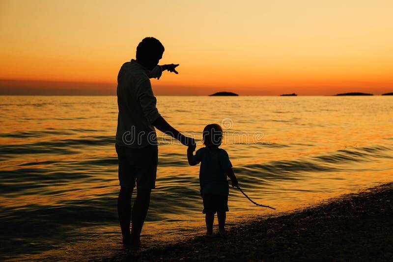 Siluetas traseras del padre y del hijo que caminan por el mar fotos de archivo libres de regalías