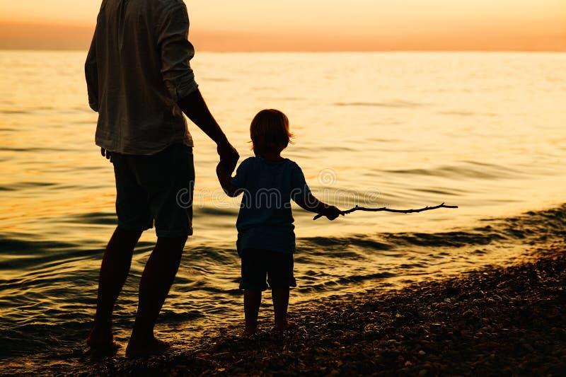 Siluetas traseras del padre y del hijo que caminan por el mar imagen de archivo