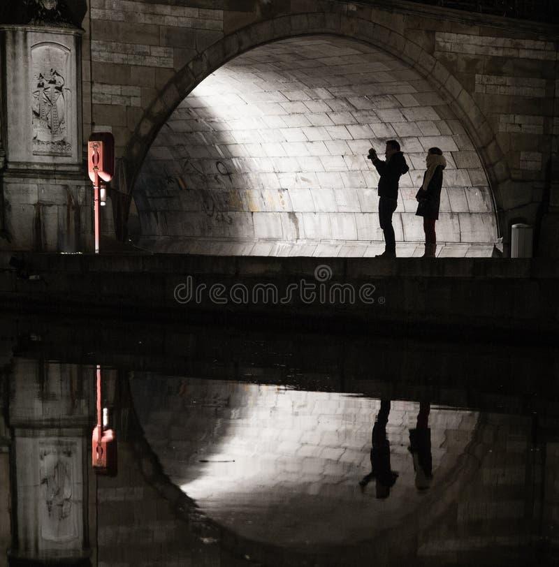 Siluetas y reflexiones de turistas debajo de un puente medival imagen de archivo