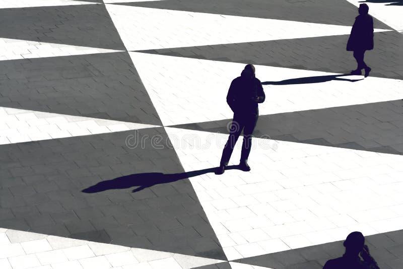 Siluetas y sombras de la gente que se coloca en un cuadrado abierto fotografía de archivo