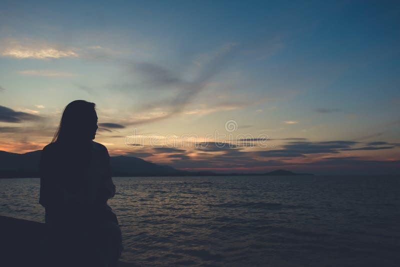 Siluetea imagen de una mujer que mira la opinión del mar sobre la playa con puesta del sol foto de archivo