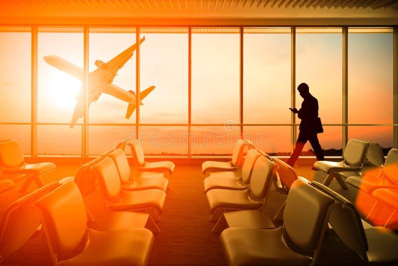 Silueteado del teléfono móvil del uso del hombre en aeropuerto en la puesta del sol Busine imagen de archivo