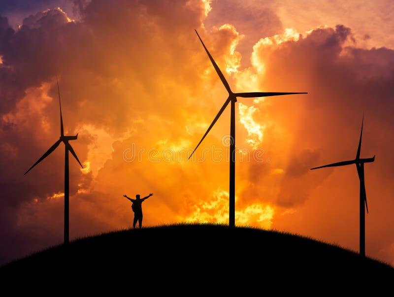 Siluetee al backpacker del hombre que la situación aumentada encima de los brazos celebra con las turbinas de viento que generan  imágenes de archivo libres de regalías