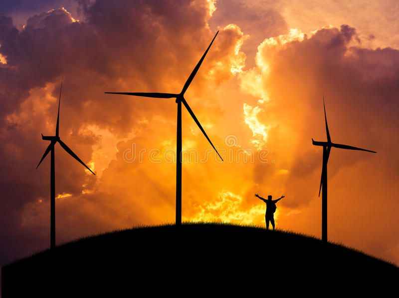 Siluetee al backpacker del hombre que la situación aumentada encima de los brazos celebra en la colina con las turbinas de viento foto de archivo libre de regalías