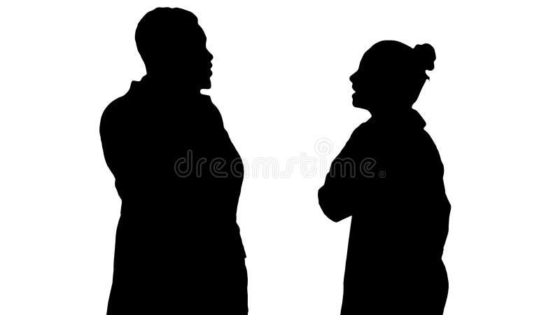 Siluetee al doctor de sexo femenino y de sexo masculino usando los teléfonos móviles que hacen las llamadas que dicen noticias fe fotografía de archivo libre de regalías