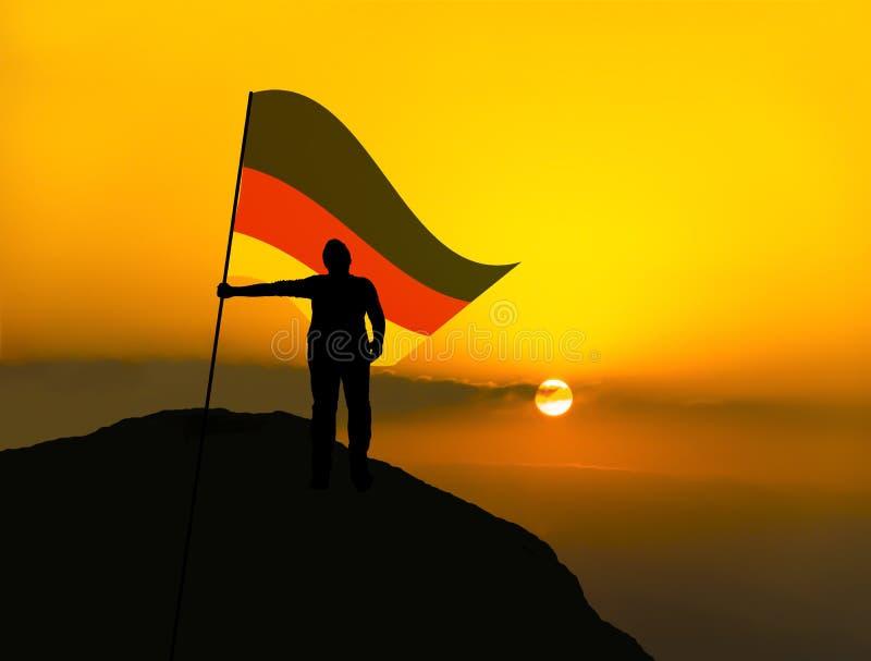 Siluetee al ganador del hombre que agita la bandera de Alemania encima del pico de montaña imagen de archivo