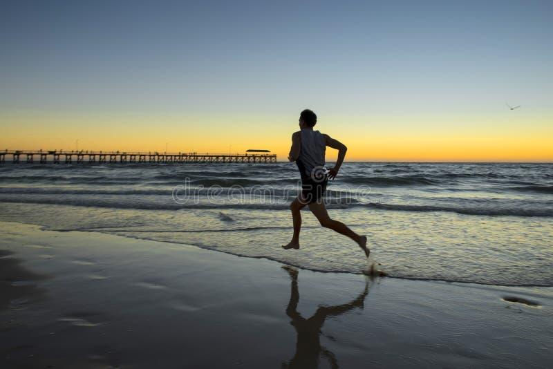Siluetee al hombre dinámico joven del corredor del atleta con el entrenamiento fuerte del cuerpo del ajuste en la playa de la pue foto de archivo