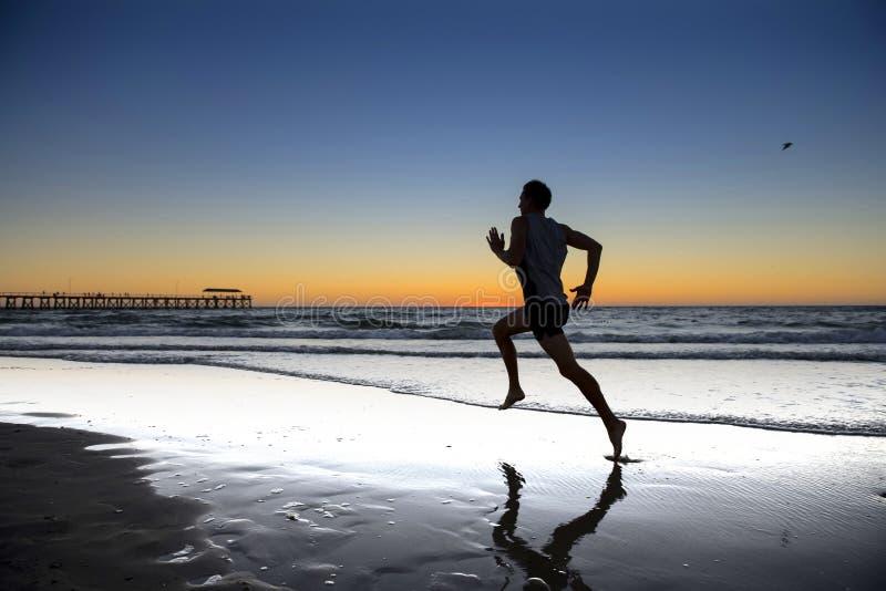 Siluetee al hombre dinámico joven del corredor del atleta con el entrenamiento fuerte del cuerpo del ajuste en la playa de la pue fotos de archivo