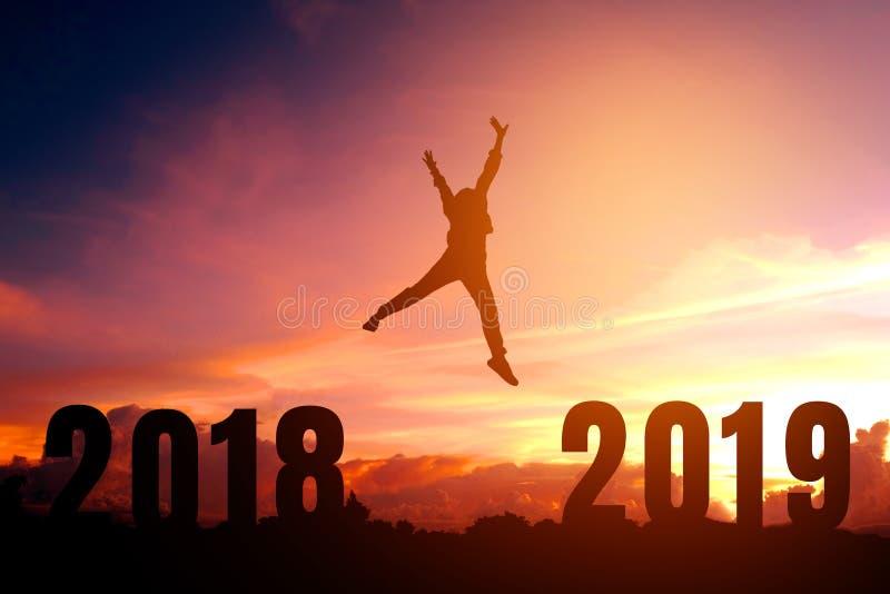 Siluetee al hombre joven feliz a 2019 Años Nuevos imagenes de archivo