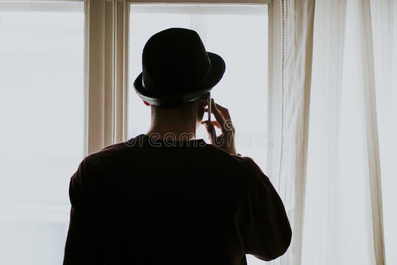Siluetee al hombre joven retroiluminado que habla en el teléfono fotos de archivo