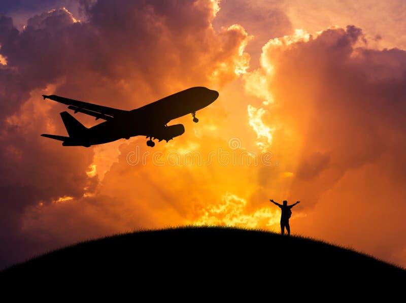 Siluetee al hombre que la situación aumentada encima de los brazos celebra durante el aeroplano saca foto de archivo