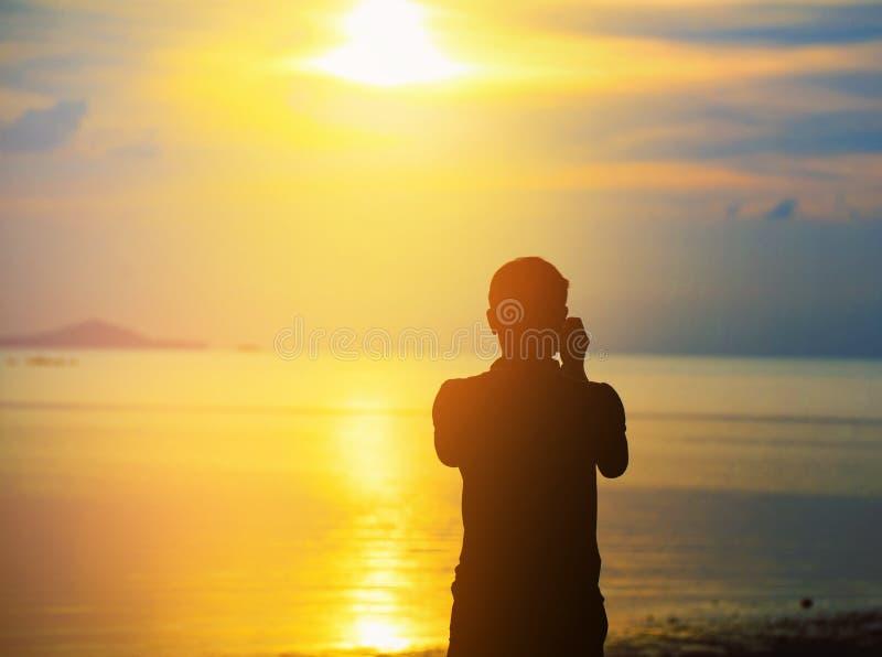 Siluetee al hombre que toma las fotos de la puesta del sol con la cámara imagen de archivo libre de regalías